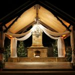 Gazebo With Awesome Chandelier Lighting And Long Curtains Near Stone Fireplace