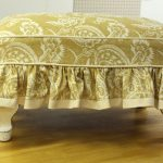 Gold toned slipcover for an ottoman with floral motif