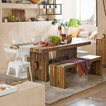 Hardwood dining table in rectangular shape and without coat a wooden bench three units of white modern chairs for a modern dining room