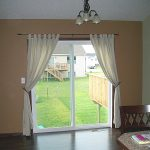 Patio Sliding Door With White Curtains in Room With Small Chandelier