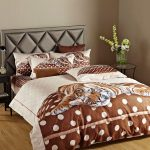 Queen sized bed frane with black leather headboard and large  tiger pictured bedcover some pillows with tiger pictured pillowcases small black coat wood bedside table with small drawer