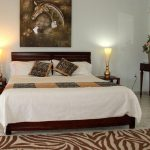 Simple safari bedroom decorating idea with zebra themed pillowcases and zebra skin theme bedroom rug