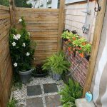 Small And Simple Outdoor Shower Design With Semi Free Standing Showerhead Fixture Wood Plank Panels And Some Decorative Plants