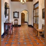 Spanish tile flooring idea with motif a console table a wooden chair a decorative pendant lamp wooden ceiling idea