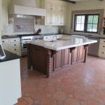 Spanish tile flooring in mixed shaped for kitchen floor a large kitchen island with white marble top and finest crafted wooden base L shaped kitchen counter with black top white kitchen cabinet