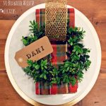 Take a wreath form and cover it with pine leaves. using glue and strings and place on the dining plate. Write the name in long rectangular white sheet of paper and place it over the green wreath