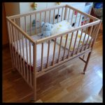 Unfinished wooden baby cribs IKEA with mattress pillow and an animal stuff