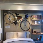 Wall mount bike rack over the headboard of a bed frame