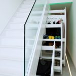 White Cupboard Under the Stairs With Glass Stairs Holder