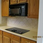 White Kitchen With Built In Stove Top And Wooden Kitchen Cabinet