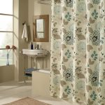 White fabric shower curtain with floral pattern metal curtain rod with ring clips built in bathtub  bathroom sink and faucet with metal base square mirror with brown frame brown bathroom rug