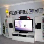 White modern minimalist TV stand with under shelves for media players a pair of higher cabinet units in white a pair of cordless table lamps a line of picture frame arrangement