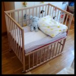 Wooden IKEA baby cribs with removable panel and mattress pillow and an animal stuff