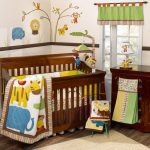 Wooden baby crib with safari themed blanket some animal stuffs safari wallpaper idea cute table lamp with animal miniature as decoration