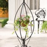 adorable black wrought iron stand for flower design with natural colored potted plant and adorable legs