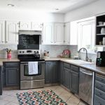 adorable classic gray kitchen design with white gray wooden cbainetry and patterned area rug and tile flooring and white siding and wall racks