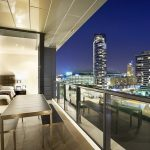 adorable design if balcony in apartment with city view and glass railing and wooden floor and dining set