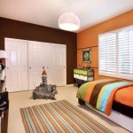 adorable modern bedroom color ideas with orange painted wall and bedding with ombre sheet and white closet and stripe patterned area rug