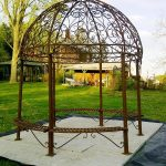adorable round wrought iron pergola with bench at each side plus round decorative floor with attractive ornaments