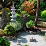 adorable small japanese garden idea with concrete patio with thin temple and stone decoration and hydrangea and trees