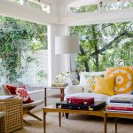 adorable sunroom design idea with white tufted couch and colorful cushions and glass window and white siding and glass slim coffee table and lattice box end table