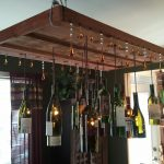 adorable wooden wine bottle chandelier with holes with wire suspension in dining table with glass window