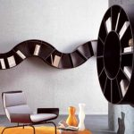 adrable black cool bookshelves design with curving style on the wall and round slots and modern chair and orange area rug