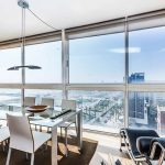 Amazing Dining Place Design With White Chairs And Glass Table And Black Reclining Chair And Open Plan Of Apartment With City View