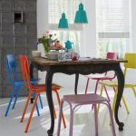 amazing rustic and vinatge wooden dining table with blue orang epink yellow and purple chairs with turquoise pendants with open plan