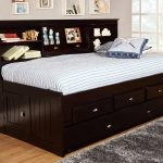 appealing daybeds with storage made of wood in dark brown finishing with drawer beneath and headboard with storage adorned with accessories and grey rug and wooden floor