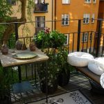 attractive apartment balcony furniture with wooden bench and square table plus awesome plants and modern white black rug