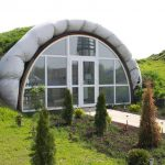 awesome underground home eco friendly design with half circle shape with glass siding and unique facade and concrete walkway