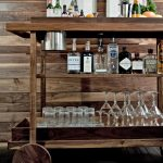 bar cart accessories on wooden bar cart with exclusive wine and glasses and liquors and wooden wall and pictures on wall