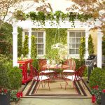 beautiful outdoor patio with red seating design with white pergola with clematis with area rug and green garden