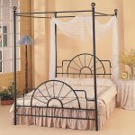 black iron canopy bed frame with tranpararents clothes and fancy comforter set plus unique standing lamp and night table with patterned table cloth