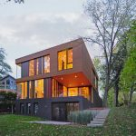 Boxy Shaped Modern Compact House Design With Open Plan And Gray Beige Siding Wall And Golden Lighting And Grassy Meadow