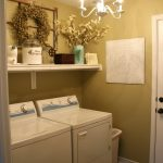 calming basement laundry room design with yellow painted wall and white washing machine and wall rack and chandelier and brown flooring