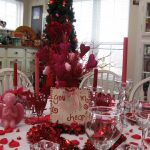 cheerful red christmas table centerpiece idea with white cloth and white chairs and red flowers and acrylic candle holder