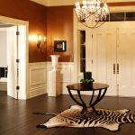 classi home design idea with foyer decoration with zebra area rug and round wooden table with chandelier and double tone wall paint idea