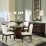 classic 40 round dining table with tulip wooden base and white chairs plus fascinating rug and cool sideboard with double table lamps