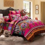 classic bedroom design idea with hot pink tribal patterned bedding idea with carved headboard and faux rug and glass door and wooden floor