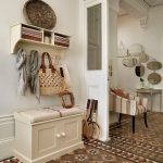 classic white carved hall storage idea with floating rack and hooks and patterned area rug beneath white painted wall with chair