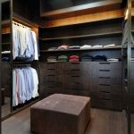 classy and exclusive dressing room design with black wooden storage and pouff and wooden floor and cabinet lighting