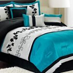 classy black white and turquoise accent on a luxurious bedding with small black table and indoor plant and glass window and white floor lamp