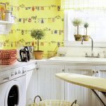 colorful basement laundry room design with yellow patterned wallpaper and indoor plants with iron board and white cabinetry