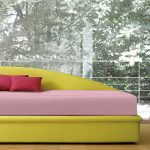 colorful daybed design idea with yellow frame and pink upholster and red cushions and green hooks and green storage box and floor to ceiling glass window