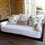 comfortable rattan porch swing set with jute rop and white upholster and colorful cushions above wooden floor with brick wall accent