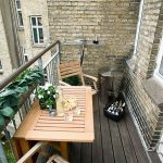compact apartment balcony furniture with folding wooden table and chairs plus wall mounted shelf and steel trashcan plus plants and brick wall