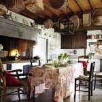 country style rustic kitchen design with pink floral table cloth and black chairs and cutelry hooks storage and gray cabinet