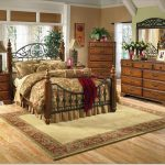 cozy bedroom with oxford creek furniture consisting of king size metal bedframe plus brown persian rug plus wooden dressee and awesome hardwood floor and nightstand